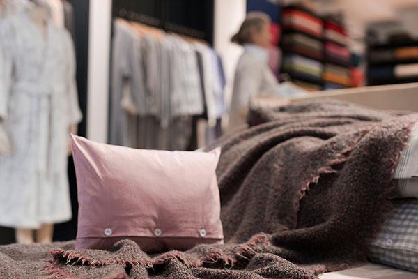 Stoffkontor Ladengeschäft Bett mit Kissen und Wolldecke
